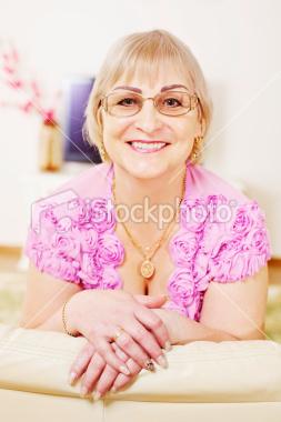 Stock-photo-17867205-cheerful-mature-woman-on-sofa